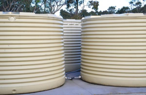 Three large cream coloured rainwater tanks
